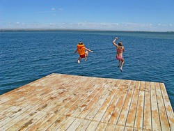 Children in swimsuits jump from the pier into the water. Vacation at sea. Children's rest.