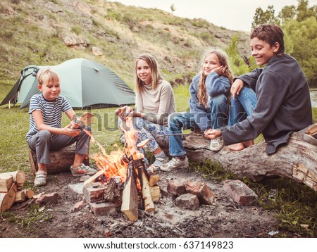 Children in the camp by the bonfire. Group teen outdoors at summer