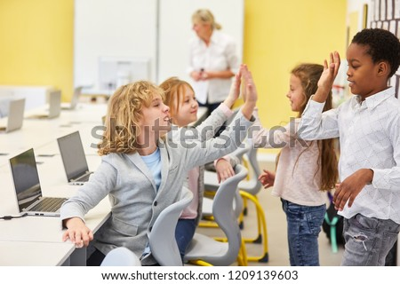 Children in the elementary school elementary school give themselves a high five in the computer course #1209139603
