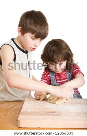 children in the kitchen making a dough