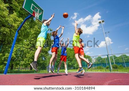 Children jump for flying ball during basketball
