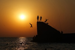 Children jump from the pier into the sea. Silhouettes at sunset. Summer travel.