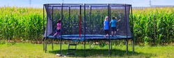 Children jump, run, trampolining in Open Jump Trampoline. Garden big Trampoline on the green grass near the corn field. Outdoor Trampoline with safety net with Zipper entrance, banner