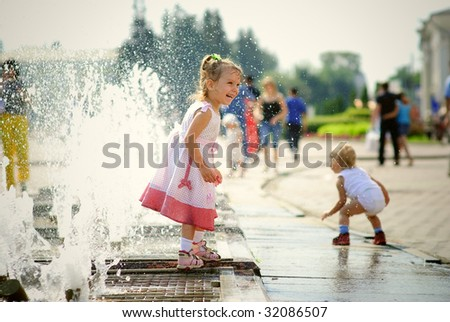 Children laugh and played in city fountain.