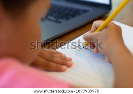 Children learning how to write the alphabet, pencil and notebook. School online. Handwriting. Stock photo ©