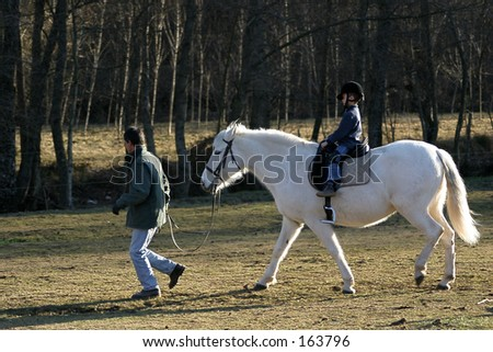 Children learning to ride a horse