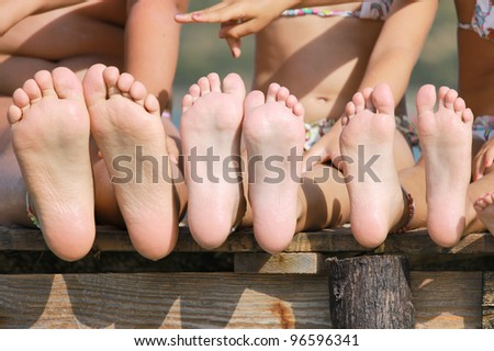 Children legs by the sea - stock photo