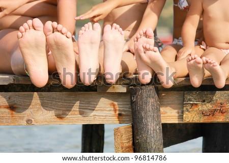 Children legs on the wooden pier