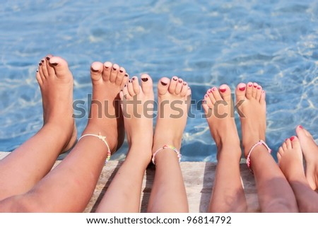 Children legs on the wooden pier above the sea