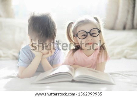 Children lie on the bed next to the newborn baby, little sister. Children's emotions.