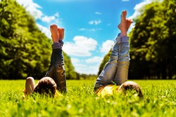 children lie on the bright green grass and hold their feet up
