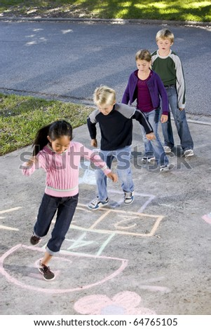 Children lined up on driveway, playing hopscotch.  Ages 7 to 9.