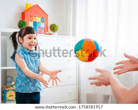 children little girl play in a children's game room, throwing ball. concept of interaction parent and kid, communication, mutual play, quarantine, self-isolation home, education.