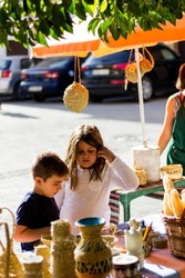 children looking at a handicraft stand with wickerwork objects