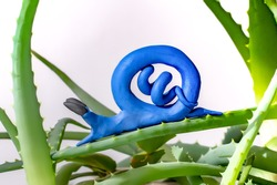 children made little blue soft modeling clay snail sitting on green leaf