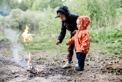 children make a fire in the forest.children indulge in fire is very dangerous. two boys try to light a fire with twigs while in the forest.two guys stand in the forest in spring time.