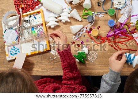 Children make crafts and toys, christmas tree and other. Painting watercolors. Top view. Artwork workplace with creative accessories. Flat lay art tools.