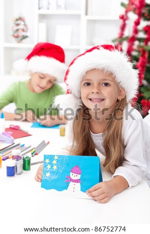 Children making christmas greeting cards wearing santa hats