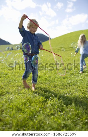 Children Making Giant Bubbles In Countryside