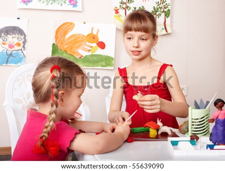 Children mould plasticine in playroom.
