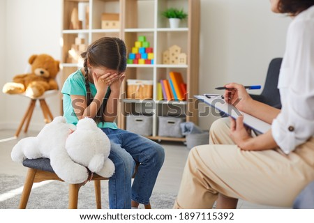 Children need help. Bullied little schoolgirl crying in psychologist's office unable to control emotions, sharing problems and traumas. Professional psychotherapist talking to distressed bully victim Сток-фото ©