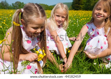 Children on a beautiful sunlit meadow in spring on an Easter egg hunt having just found a nest