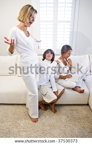 Children on laptop on white living room sofa with mom watching