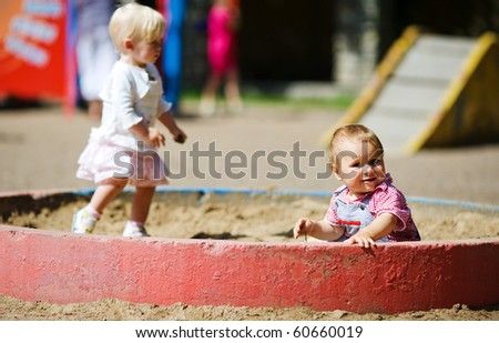Children on playground in sandbox boy and girl