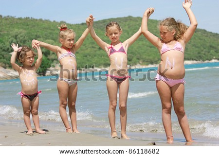 children on the beach with sun lotion
