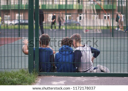 Children on the playground in the summer afternoon relax after a game of football. playing outside, playing outdoors, outdoor games, outdoor activities, outdoor recreation, park, parks #1172178037