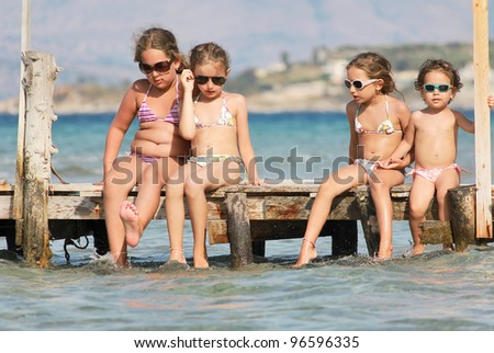 Children on the wooden pier by the sea
