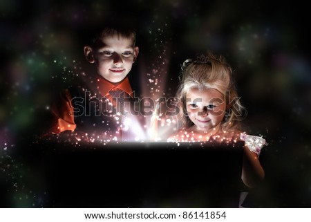 Children opening a magic gift box with lights and shining around