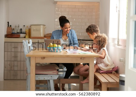 Children Paint At Kitchen Table As Mother Works At Laptop #562380892