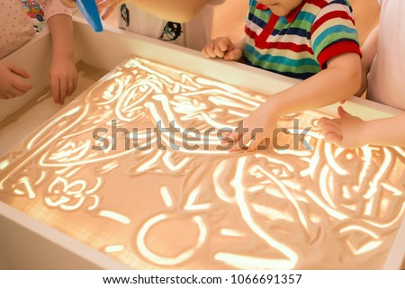 Photo of Children paint in the interactive sand table , sand animation