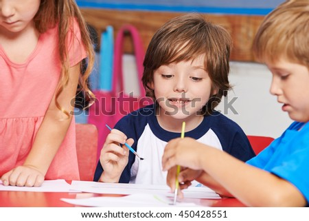 Children painting images with water color in art class in elementary school