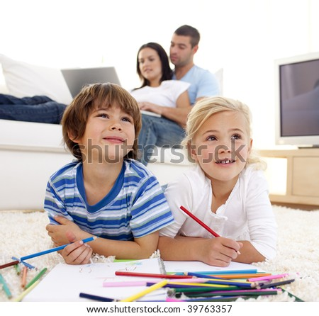 Children painting in living-room and parents using a laptop on sofa - stock photo