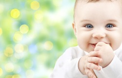 children, people, infancy and age concept - beautiful happy baby over green lights background
