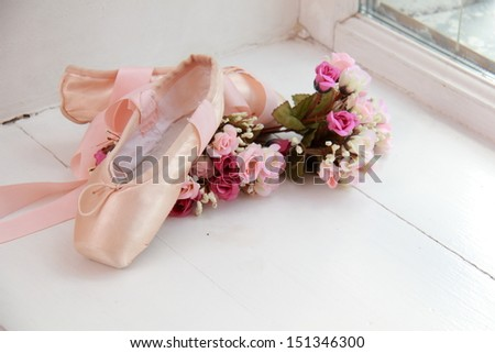Children pink pointes with ribbons lay on the windowsill next to white flowers