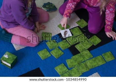 children play cards table game #1034854990