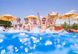 Children play fun with splashes on the side of the pool at the resort