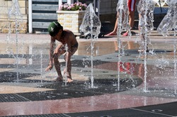 Children play, have fun in the water of the fountain. Summer vacation. Happy childhood concept. Children splash in the city fountain. The child catches the stream of the fountain.