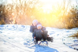 Children play in a snowy winter park at sunset. Friends sledding from a hill and having fun. Winter fun. Holidays.