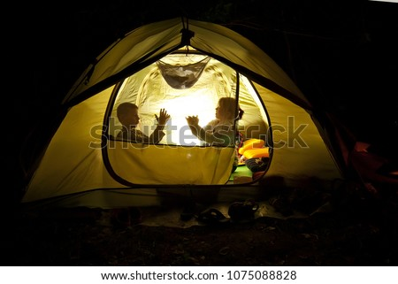 children play in the hike. the tent lights at night from the flashlight. dark silhouettes of children. #1075088828
