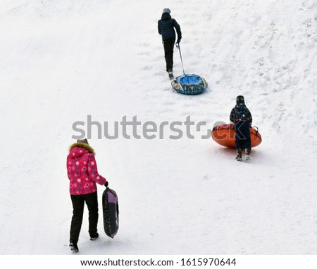 Children play in the winter in nature. Rest in a winter park on a tubing.  Back view. Active games. Healthy lifestyle, outdoor activities.  Climb a snow hill.