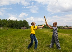 Children play outdoors in the park and fight with wooden swords.