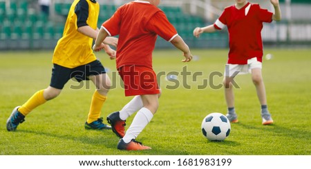 Children play soccer game on grass venue. Kids kicking soccer ball. Boys in red and yellow soccer jersey and soccer cleats