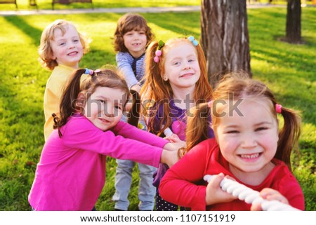 Children play tug of war in the park. Children's Day, June 1, friendship, childhood, vacation, camp #1107151919