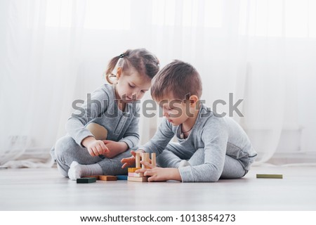 Children play with a toy designer on the floor of the children's room. Two kids playing with colorful blocks. Kindergarten educational games.