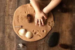 Children play with salt dough on the kitchen table. Hands mold clay with their own hands to create homemade zero-waist toys. Creative lesson with a test of natural products. Development of children in
