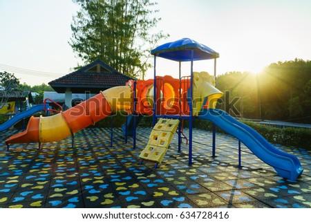 Children playground  activities in public park at sunlight morning. Children run, slide, swing,seesaw on modern playground. #634728416